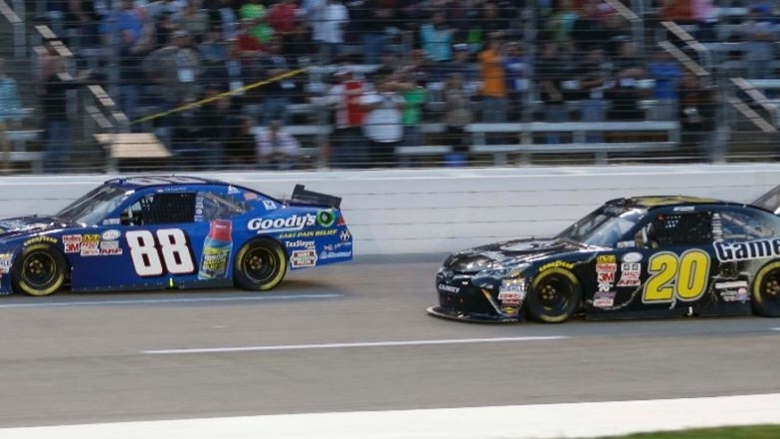 Dale Earnhardt Jr. (88) races against Erik Jones (20) during the NASCAR Xfinity series auto race at Texas Motor Speedway in Fort Worth, Texas, Friday, April 10, 2015. (AP Photo/Tim Sharp)