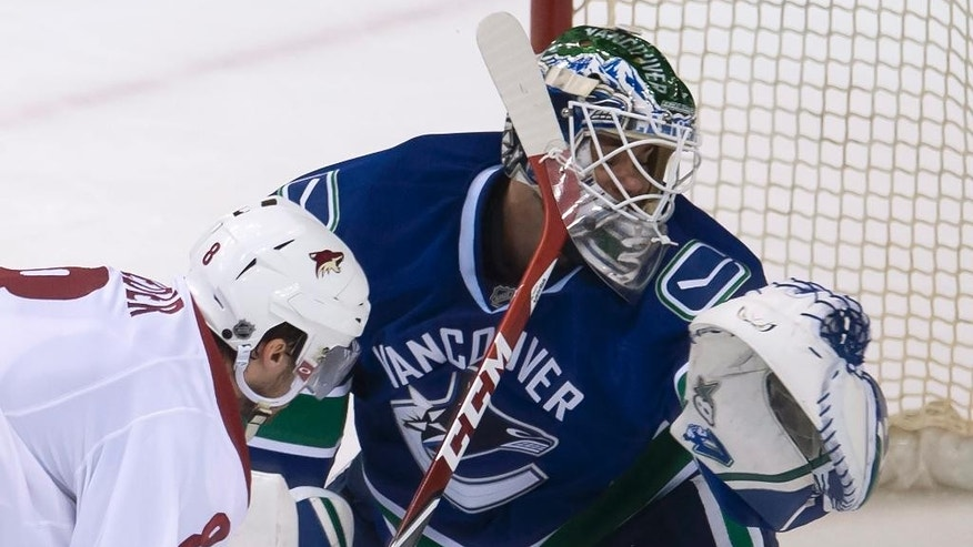 Vancouver Canucks goalie Eddie Lack (31) makes a save on Arizona Coyotes center Tobias Rieder (8) during the third period of an NHL hockey game Thursday, April 9, 2015, in Vancouver, British Columbia. (AP Photo/The Canadian Press, Jonathan Hayward)