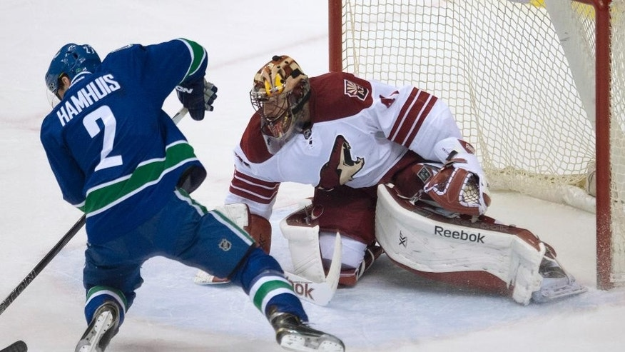 Vancouver Canucks defenseman Dan Hamhuis (2) tries to get a shot past Arizona Coyotes goalie Mike Smith (41) during the second period of an NHL hockey game Thursday, April 9, 2015, in Vancouver, British Columbia. (AP Photo/The Canadian Press, Jonathan Hayward)