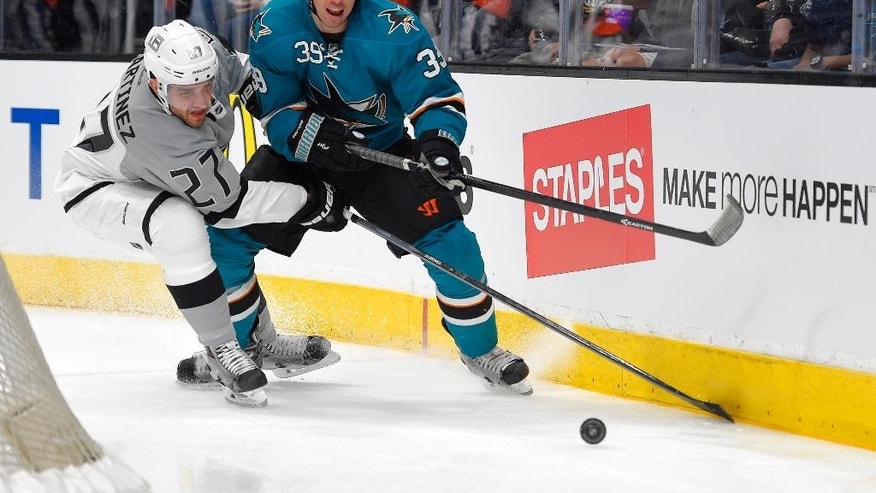 Los Angeles Kings defenseman Alec Martinez, left, and San Jose Sharks center Logan Couture battle for the puck during the first period of an NHL hockey game, Saturday, April 11, 2015, in Los Angeles. (AP Photo/Mark J. Terrill)