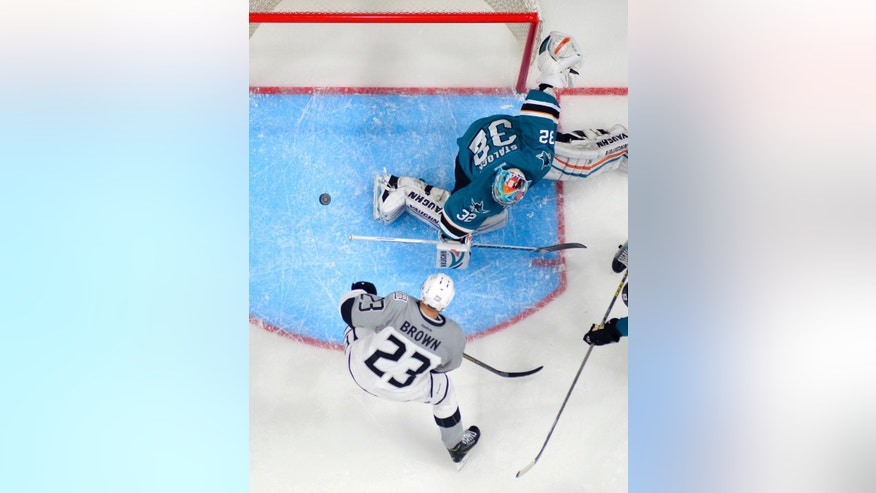 San Jose Sharks goalie Alex Stalock, top, stops a shot by Los Angeles Kings right wing Dustin Brown during the first period of an NHL hockey game, Saturday, April 11, 2015, in Los Angeles. (AP Photo/Mark J. Terrill)