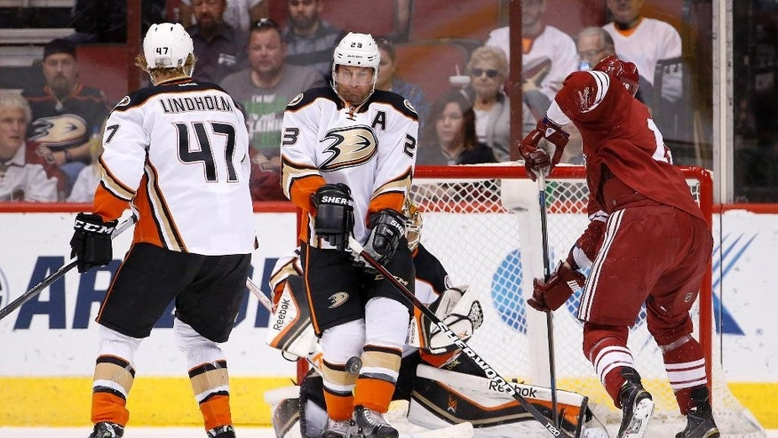 Anaheim Ducks' Francois Beauchemin (23) blocks a shot in front of goalie Frederik Andersen, of Denmark, as Ducks' Hampus Lindholm (47), of Sweden, and Arizona Coyotes' David Moss, right, both look on during the first period of an NHL hockey game Saturday, April 11, 2015, in Glendale, Ariz. (AP Photo/Ross D. Franklin)
