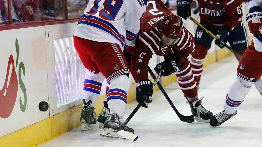 Washington Capitals defenseman Matt Niskanen (2) passes the puck past New York Rangers right wing Jesper Fast (19), from Sweden, in the first period of an NHL hockey game, Saturday, April 11, 2015, in Washington. (AP Photo/Alex Brandon)