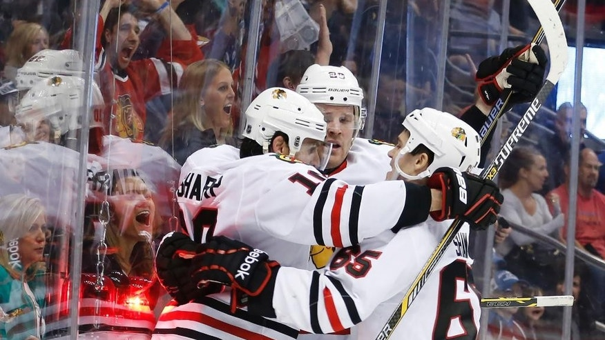 Chicago Blackhawks left wing Patrick Sharp (10) celebrates his goal against the Colorado Avalanche with teammates Andrew Shaw (65) and Bryan Bickell (29) during the second period of an NHL hockey game Saturday, April 11, 2015, in Denver. (AP Photo/Jack Dempsey)
