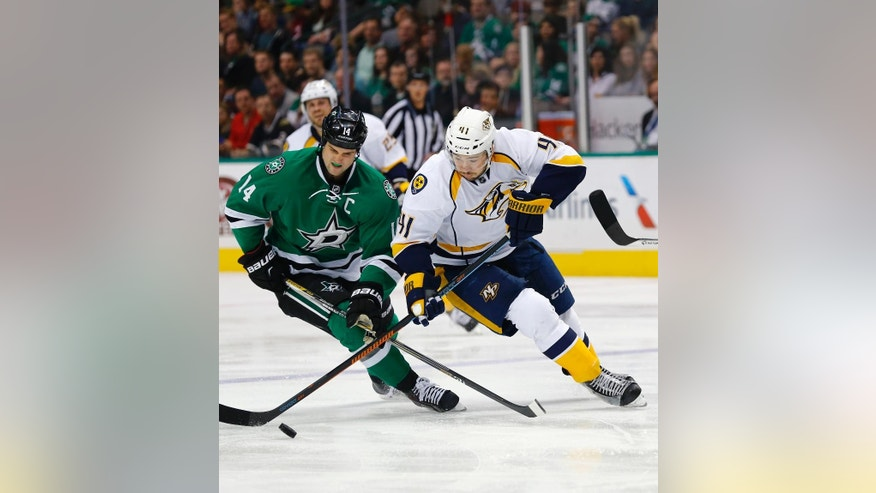 Dallas Stars' Jamie Benn (14) and Nashville Predators' Taylor Beck (41) battle for the puck during the second period of an NHL hockey game, Saturday, April, 11, 2015, in Dallas. (AP Photo/Mike Stone)