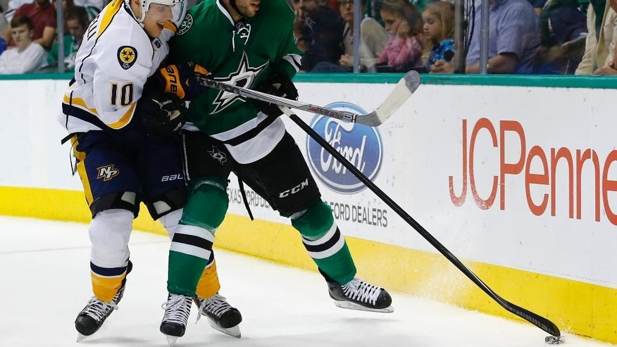 Nashville Predators' Mike Santorelli (10) and Dallas Stars' Jason Demers (4) battle for the puck during the second period of an NHL hockey game, Saturday, April, 11, 2015, in Dallas. (AP Photo/Mike Stone)