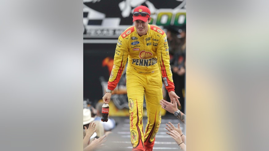 Sprint Cup Series driver Joey Logano walks onto the track during introductions before the NASCAR auto race at Texas Motor Speedway in Fort Worth, Texas, Saturday, April 11, 2015. (AP Photo/Ralph Lauer)