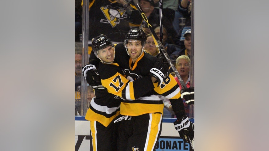 Pittsburgh Penguins' Blake Comeau (17) and Brandon Sutter (16) celebrate a goal by Sutter during the second period of an NHL hockey game against the Buffalo Sabres Saturday, April 11, 2015, in Buffalo, N.Y. (AP Photo/Gary Wiepert)