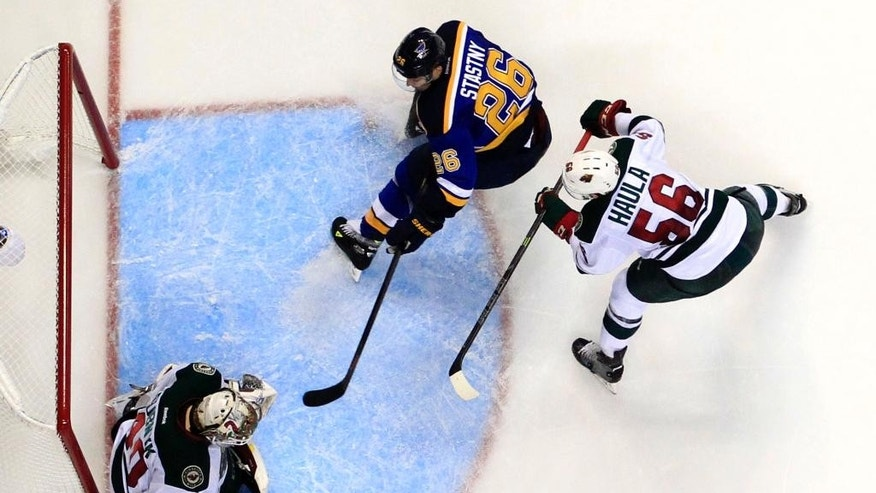 Minnesota Wild goalie Devan Dubnyk, left, deflects a puck as teammate Erik Haula, of Finland, and St. Louis Blues' Paul Stastny (26) watch during the second period of an NHL hockey game Saturday, April 11, 2015, in St. Louis. (AP Photo/Jeff Roberson)