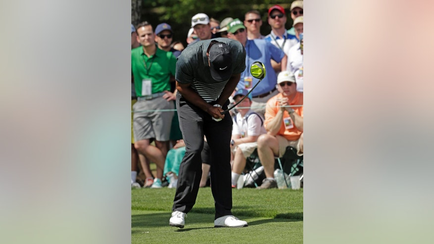 Tiger Woods reacts to his tee shot on the ninth hole during the third round of the Masters golf tournament Saturday, April 11, 2015, in Augusta, Ga. (AP Photo/Chris Carlson)