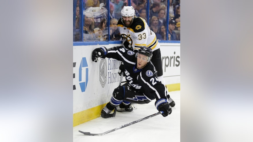 Tampa Bay Lightning right wing Ryan Callahan (24) is knocked down by Boston Bruins defenseman Zdeno Chara (33), of Slovakia, during the second period of an NHL hockey game Saturday, April 11, 2015, in Tampa, Fla. (AP Photo/Chris O'Meara)