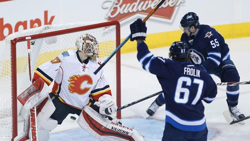 Winnipeg Jets' Michael Frolik (67) and Mark Scheifele (55) celebrate Drew Stafford's (12) goal against Calgary Flames goaltender Joni Ortio (37) during the first period of an NHL hockey game, Saturday, April 11,  2015 in Winnipeg, Manitoba.  (John Woods/The Canadian Press via AP)   MANDATORY CREDIT