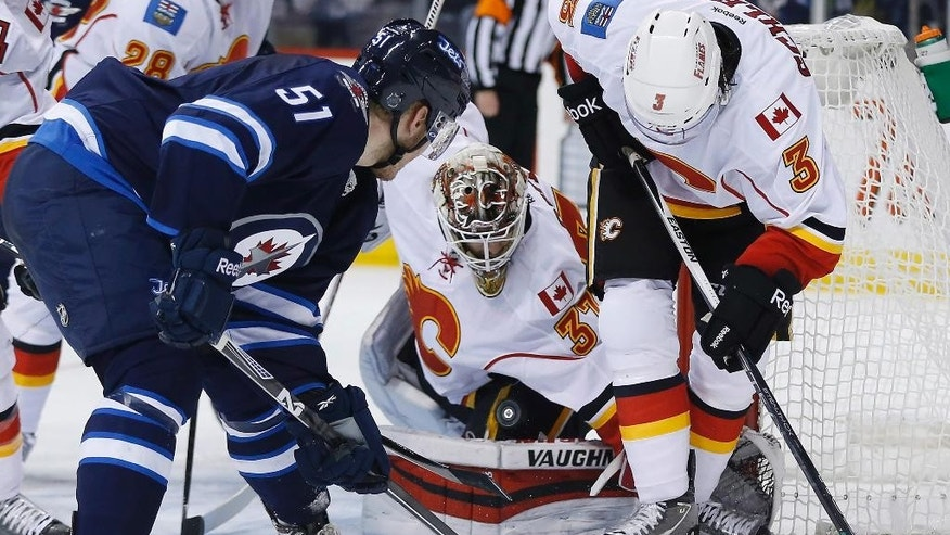 Calgary Flames goaltender Joni Ortio (37) keeps his eye on the rebound as Winnipeg Jets' Andrew Copp (51) and Flames' David Schlemko (3) attempt to recover it during the second period of an NHL hockey game, Saturday, April 11,  2015 in Winnipeg, Manitoba.  (John Woods/The Canadian Press via AP)   MANDATORY CREDIT