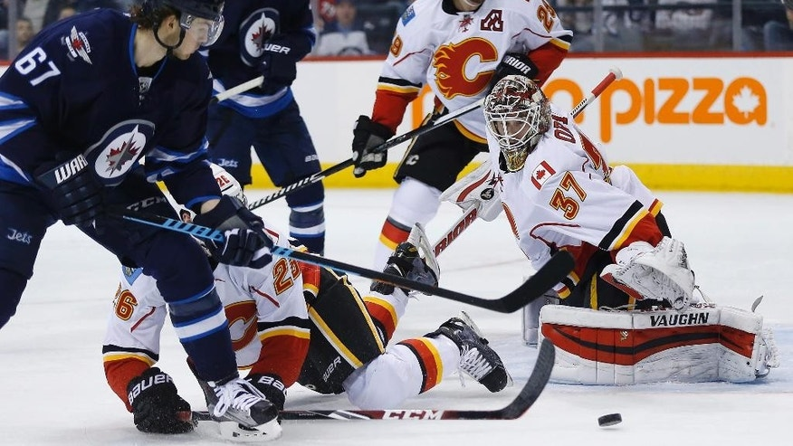 Calgary Flames goaltender Joni Ortio (37) saves the shot from Winnipeg Jets' Michael Frolik (67) as Flames' Tyler Wotherspoon (26) and Deryk Engelland (29) defend and Jets' Mark Scheifele (55) look on during the second period of an NHL hockey game, Saturday, April 11,  2015 in Winnipeg, Manitoba.  (John Woods/The Canadian Press via AP)   MANDATORY CREDIT