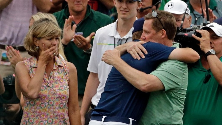 Chris Spieth, left, watches as Jordan Spieth hugs his father Shawn after winning the Masters golf tournament Sunday, April 12, 2015, in Augusta, Ga.  (AP Photo/Matt Slocum)