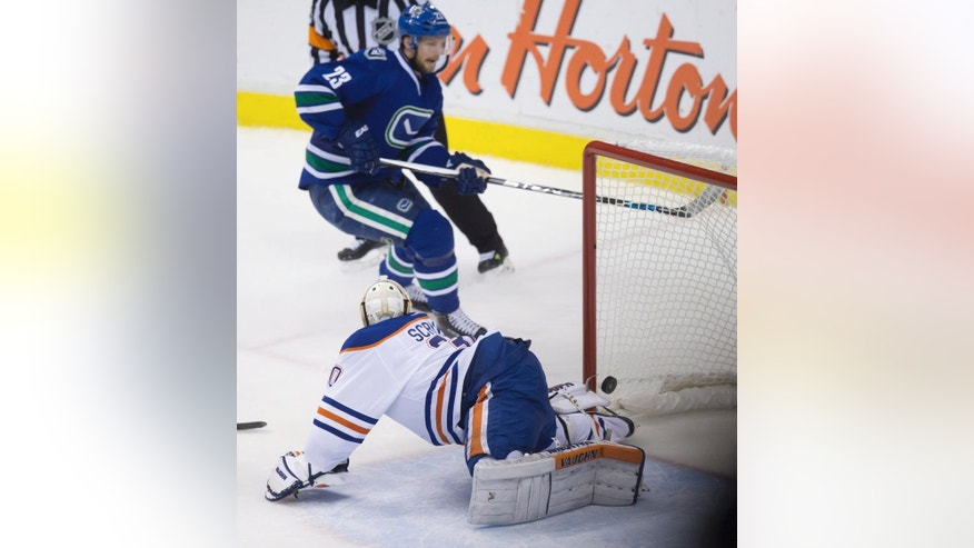 Vancouver Canucks' Alexander Edler, of Sweden, scores the winning goal against Edmonton Oilers goalie Ben Scrivens during overtime of an NHL hockey game in Vancouver, British Columbia, Saturday, April 11, 2015. (AP Photo/The Canadian Press, Darryl Dyck)