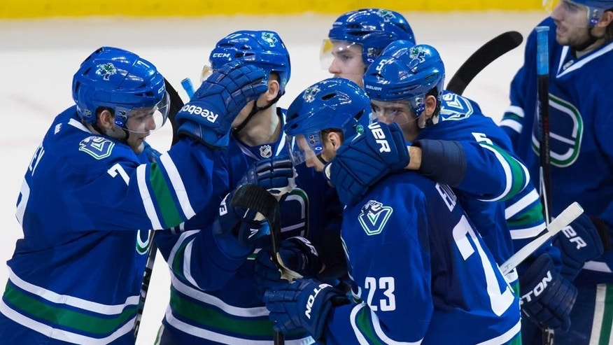 Vancouver Canucks' Alexander Edler (23), of Sweden, is mobbed by his teammates after scoring against the Edmonton Oilers during the overtime of an NHL hockey game in Vancouver, British Columbia, Saturday, April 11, 2015. (AP Photo/The Canadian Press, Darryl Dyck)