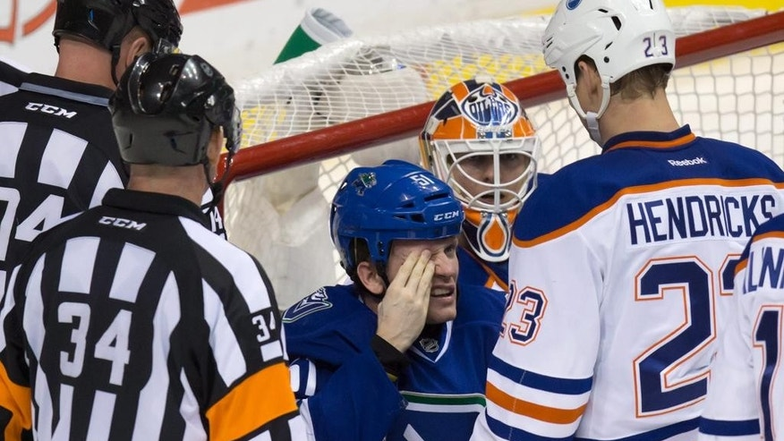 Vancouver Canucks' Derek Dorsett, center, looks up at Edmonton Oilers' Matt Hendricks, right, after Hendricks checked him to the ice during the third period of an NHL hockey game in Vancouver, British Columbia, Saturday, April 11, 2015. (AP Photo/The Canadian Press, Darryl Dyck)