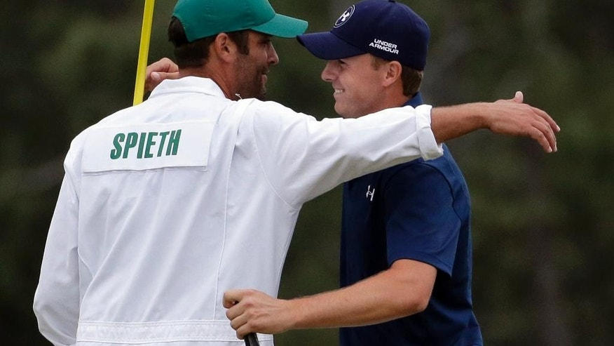 Jordan Spieth hugs his caddie Michael Greller after winning the Masters golf tournament Sunday, April 12, 2015, in Augusta, Ga.  (AP Photo/Chris Carlson)