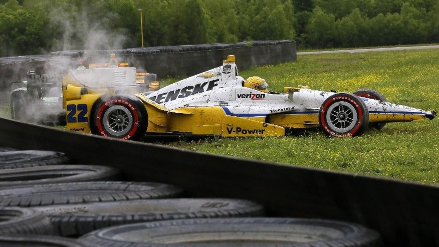Simon Pagenaud (22), of France, and Sebastien Bourdais, back left, also of France, come to a stop off the track after a crash during the IndyCar Grand Prix of Louisiana auto race, Sunday, April 12, 2015, in Avondale, La. (AP Photo/Jonathan Bachman)