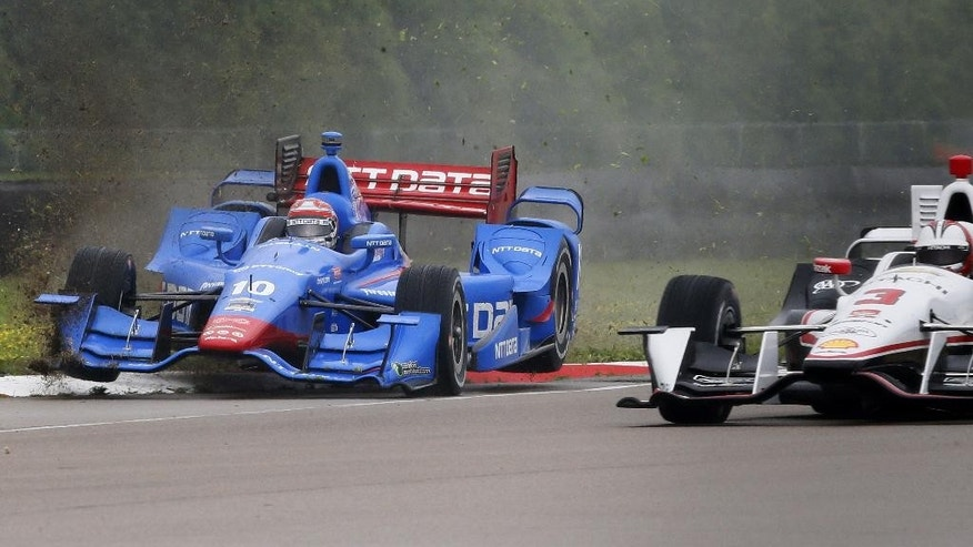 Tony  Kanaan (10), of Brazil, slips off the track to the left of Helio Castroneves (3), of Brazil, during the IndyCar Grand Prix of Louisiana auto race, Sunday, April 12, 2015, in Avondale, La. (AP Photo/Jonathan Bachman)