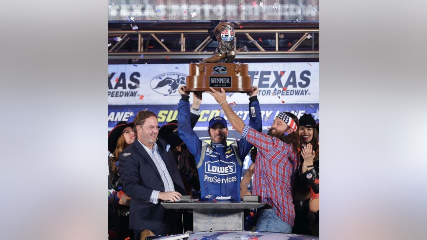 Jimmie Johnson, center, holds up the trophy with the help of Eddie Gossage and Willie Robertson after Johnson won the NASCAR Sprint Cup Series auto race at Texas Motor Speedway in Fort Worth, Texas, Saturday, April 11, 2015. (AP Photo/Tim Sharp)