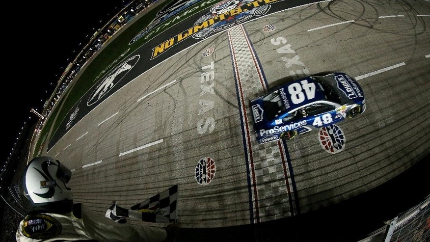 In this photo provided by NASCAR, Jimmie Johnson crosses the finish line to win the NASCAR Sprint Cup Series auto race at Texas Motor Speedway on Saturday, April 11, 2015, in Fort Worth, Texas. (AP Photo/NASCAR, Sean Gardner)