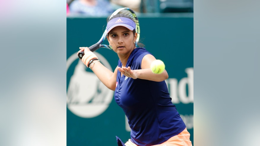 Sania Mirza, of India, returns to Alla Kudryavtseva and Anastasia Pavlyuchenkova during a doubles final match at the Family Circle Cup tennis tournament in Charleston, S.C., Sunday, April 12, 2015. Mirza and Martina Hingis won 6-0, 6-4. (AP Photo/Mic Smith)