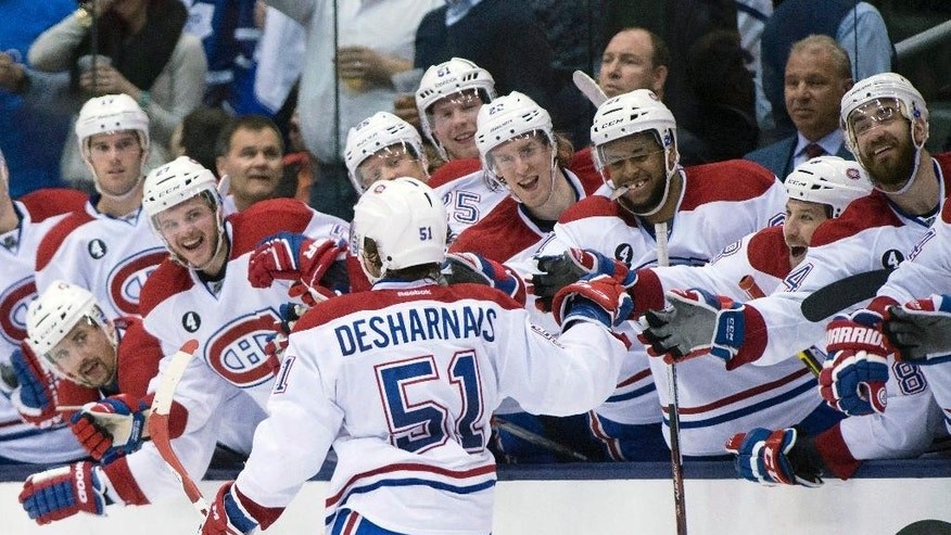 Montreal Canadiens center David Desharnais (51) is congratulated by teammates after scoring the game winning goal during an overtime shootout in an NHL hockey game, Saturday, April 11, 2015 in Toronto. (Frank Gunn/The Canadian Press via AP)   MANDATORY CREDIT