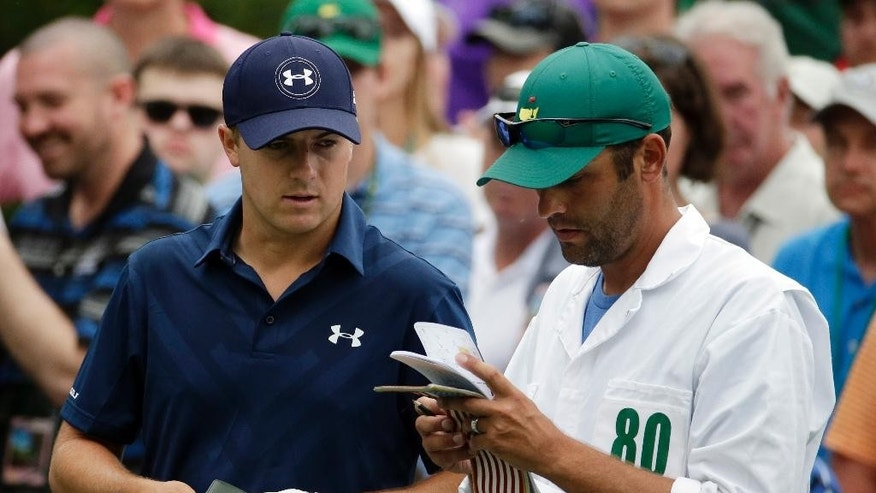 Jordan Spieth checks his course notes with his caddie Michael Greller before teeing off on the sixth hole during the fourth round of the Masters golf tournament Sunday, April 12, 2015, in Augusta, Ga. (AP Photo/Charlie Riedel)