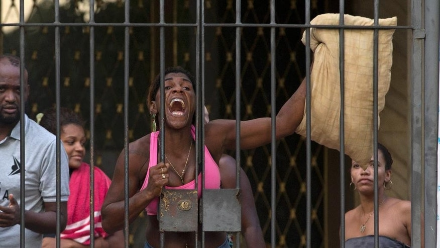A woman shouts at the police before she and others are evicted from a building they invaded about a week ago in the Flamengo neighborhood of Rio de Janeiro, Brazil, Tuesday, April 14, 2015. Police dislodged squatters from the building slated for use as a luxury hotel for the 2016 Olympics in Rio de Janeiro. (AP Photo/Silvia Izquierdo)