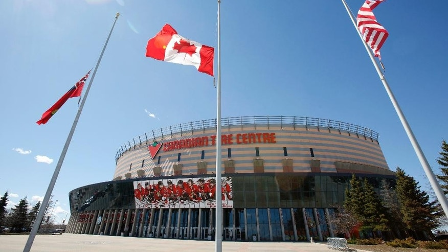 Flags fly at half-staff outside the Canadian Tire Centre in Ottawa, after the announcement of the death of Ottawa Senators assistant coach Mark Reeds, Tuesday, April 14, 2015.  (Patrick Doyle/The Canadian Press via AP)   MANDATORY CREDIT