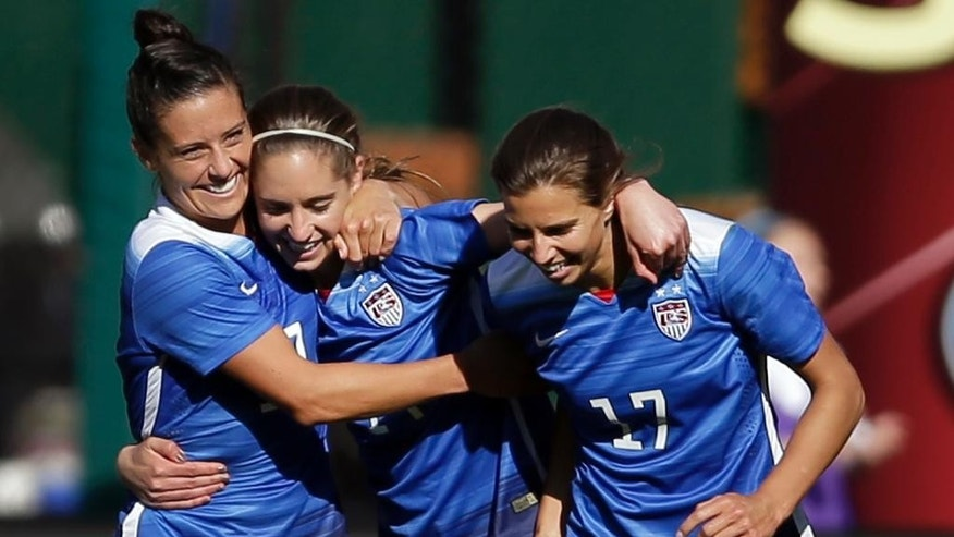 FILE - In this April 4, 2015, file photo, United States' Morgan Brian, center, is congratulated by teammates Ali Krieger, left, and Tobin Heath, after scoring during the second half of an exhibition soccer match against New Zealand in St. Louis. The trio are on the U.S. Women's World Cup roster. Coach Jill Ellis on Tuesday, April 14, 2015, announced her 23 picks for the tournament in Canada. Seeking their third title and first since 1999, the Americans open against Australia on June 8. (AP Photo/Jeff Roberson)