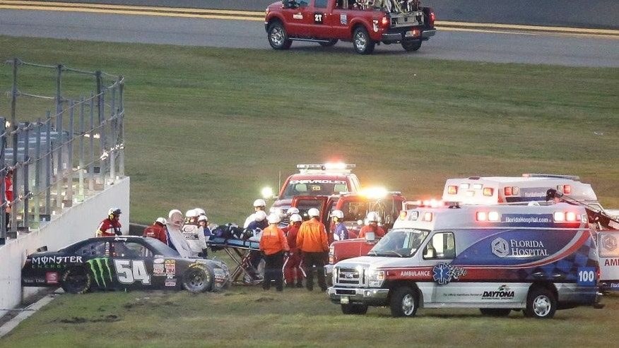 FILE - In this Feb. 21, 2015, file photo, Kyle Busch, center, is taken to an ambulance on a stretcher after he was involved in a multi-car crash during the Xfinity series auto race at Daytona International Speedway in Daytona Beach, Fla. He knew it was going to be bad when his car slid through the grass into the wall, and he knew immediately that both his leg and foot were broken. (AP Photo/John Raoux, File)