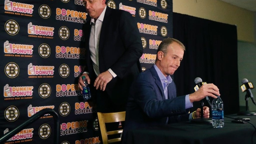 Boston Bruins President Cam Neely, left, and Bruins Chief Executive Officer Charlie Jacobs prepare to leave a news conference in Boston, Wednesday, April 15, 2015, regarding the hockey team's decision to fire general manager Peter Chiarelli days after missing the NHL playoffs for the first time in eight years. (AP Photo/Elise Amendola)