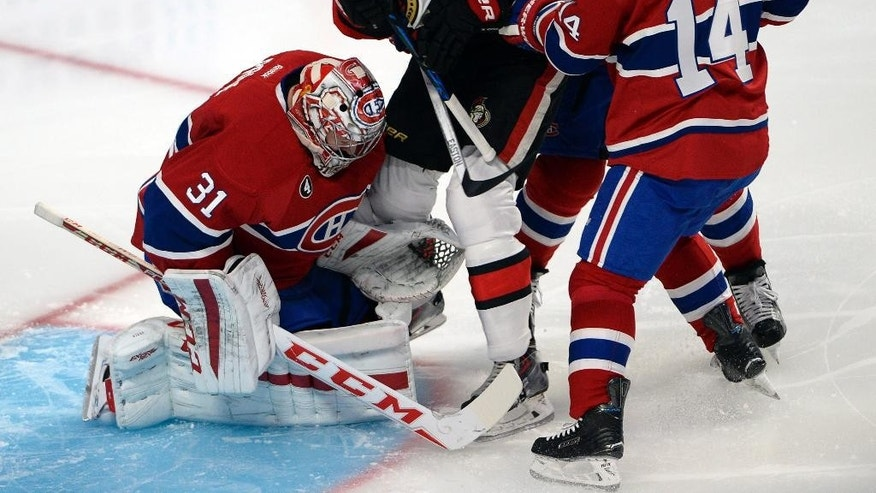 Ottawa Senators right wing Mark Stone (61) is checked into Montreal Canadiens goalie Carey Price (31) by Montreal Canadiens center Tomas Plekanec (14) and Montreal Canadiens defenseman Andrei Markov (79) during second period of the NHL Stanley Cup first round playoff hockey action Wednesday, April 15, 2015, in Montreal.  (Ryan Remiorz/The Canadian Press via AP)   MANDATORY CREDIT