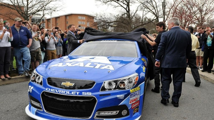 In this Tuesday, April 14, 2015, photo, NASCAR driver Jeff Gordon, right, helps pull back the tarp to unveil his street version of a blue and white Penn State race car that will be used for a June race at Pennsylvania's Pocono Raceway on the schools campus in State College, Pa. (Christopher Weddle/Centre Daily Times via AP) MANDATORY CREDIT; MAGS OUT