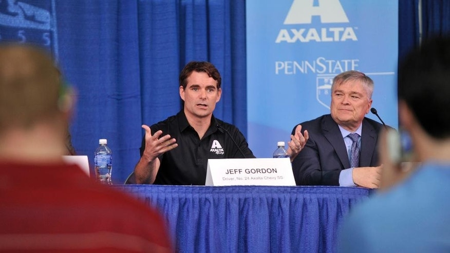 In this Tuesday, April 14, 2015, photo, NASCAR driver Jeff Gordon gestures while speaking at a press conferrence at Penn State University as Penn State president Eric Barron looks on in State College, Pa. Gordon will drive a blue and white Penn State race car in a June race at Pennsylvania's Pocono Raceway . (Christopher Weddle/Centre Daily Times via AP) MANDATORY CREDIT; MAGS OUT