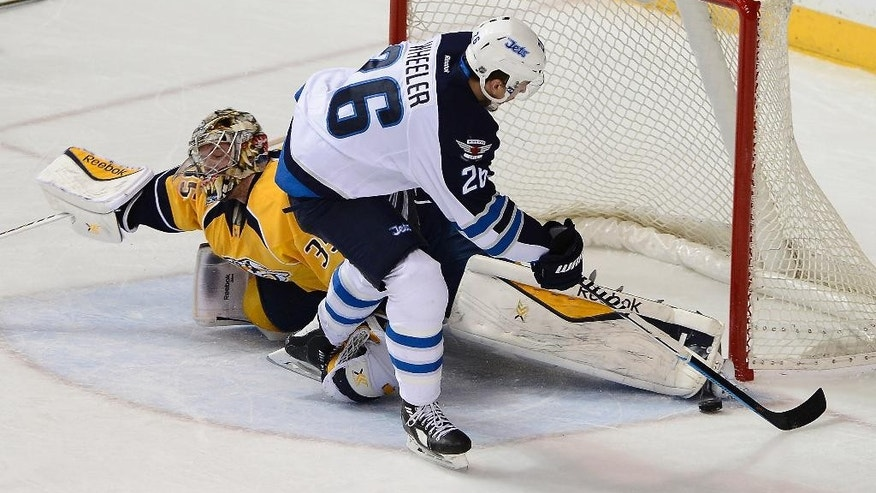 FILE - In this Feb. 12, 2015, file photo, Nashville Predators goalie Pekka Rinne, left, of Finland, blocks a shot by Winnipeg Jets right wing Blake Wheeler during the second period of an NHL hockey game in Nashville, Tenn. Today's netminders are relying on size and agility to stop shots instead of just subscribing to a certain style of goaltending. These aren't your typical butterfly goaltenders anymore, a traditional style where netminders spread their goal pads and hands to resemble a butterfly's wings.  (AP Photo/Mark Zaleski, File)