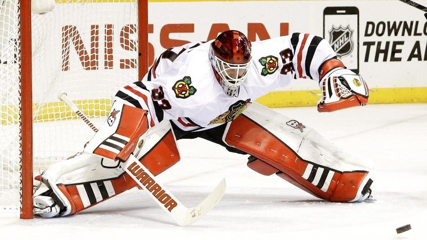 Chicago Blackhawks goalie Scott Darling reaches for the puck in the third period of Game 1 of an NHL Western Conference hockey playoff series against the Nashville Predators Wednesday, April 15, 2015, in Nashville, Tenn. (AP Photo/Mark Humphrey)