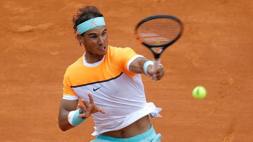 Rafael Nadal of Spain plays a return to US player John Isner during their match of the Monte Carlo Tennis Masters tournament in Monaco, Thursday, April 16, 2015. (AP Photo/Lionel Cironneau)