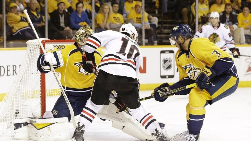 Chicago Blackhawks left wing Patrick Sharp (10) scores a goal against Nashville Predators goalie Pekka Rinne (35), of Finland, as Seth Jones (3) also defends in the second period of Game 1 of an NHL Western Conference hockey playoff series Wednesday, April 15, 2015, in Nashville, Tenn. (AP Photo/Mark Humphrey)