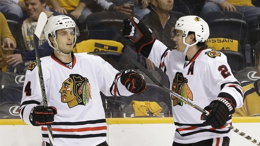 Chicago Blackhawks defenseman Niklas Hjalmarsson (4), of Sweden, is congratulated by Duncan Keith (2) after Hjalmarsson scored a goal against the Nashville Predators in the second period of Game 1 of an NHL Western Conference hockey playoff series Wednesday, April 15, 2015, in Nashville, Tenn. (AP Photo/Mark Humphrey)