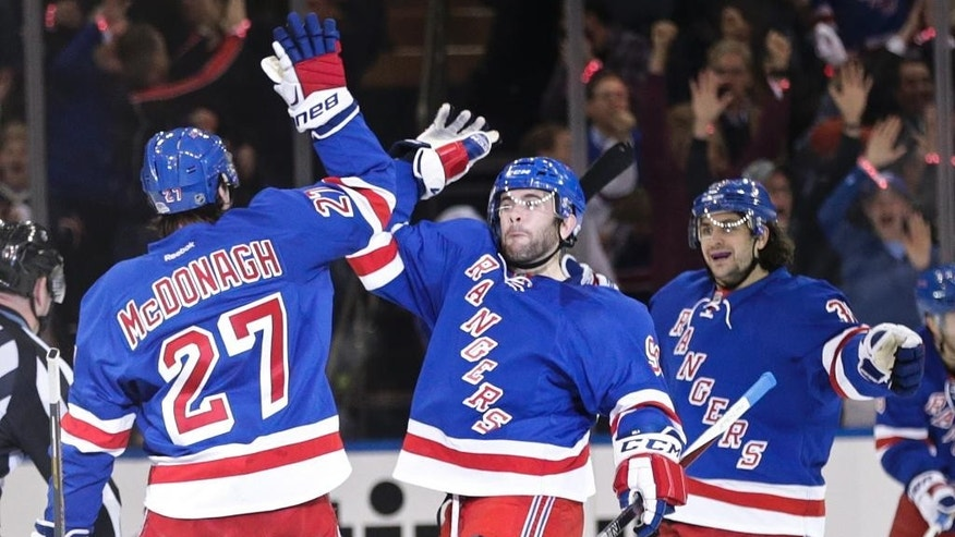New York Rangers' Ryan McDonagh, left, celebrates with teammate Keith Yandle, center, and Mats Zuccarello, right, during the first period of Game 1 in the first round of the NHL hockey Stanley Cup playoffs Thursday, April 16, 2015, in New York.  (AP Photo/Frank Franklin II)