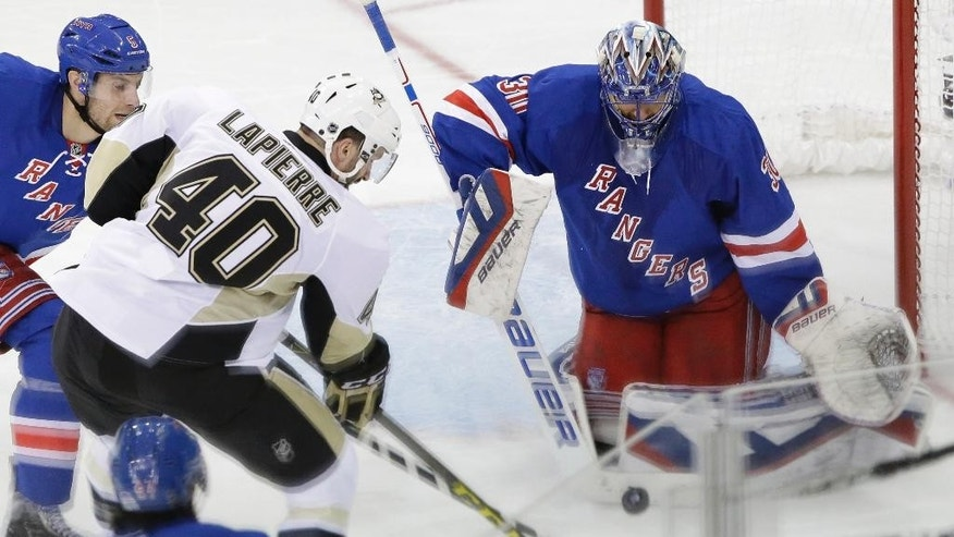 New York Rangers goalie Henrik Lundqvist (30) defends the net against a shot at goal by Pittsburgh Penguins center Maxim Lapierre (40) during the second period of Game 1 in the first round of the NHL hockey Stanley Cup playoffs, Thursday, April 16, 2015, at Madison Square Garden in New York. (AP Photo/Mary Altaffer)