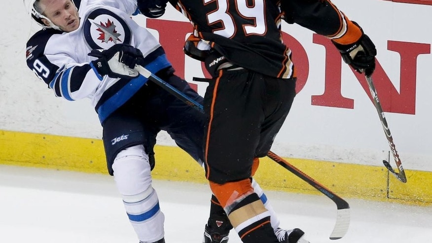 Anaheim Ducks left wing Matt Beleskey, right, checks Winnipeg Jets defenseman Tobias Enstrom during the second period of Game 1 of a first-round NHL hockey playoff series in Anaheim, Calif., Thursday, April 16, 2015. (AP Photo/Chris Carlson)