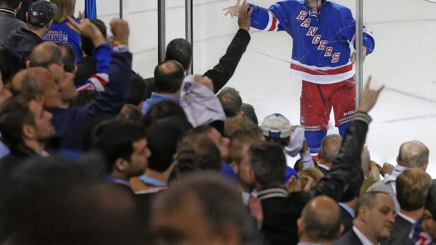 New York Rangers center Derick Brassard tosses the puck to fans after being named the game's most valuable player at the end of Game 1 in the first round of the NHL hockey Stanley Cup playoffs against against the Pittsburgh Penguins, Thursday, April 16, 2015, at Madison Square Garden in New York. The Rangers defeated the Penguins 2-1.(AP Photo/Mary Altaffer)