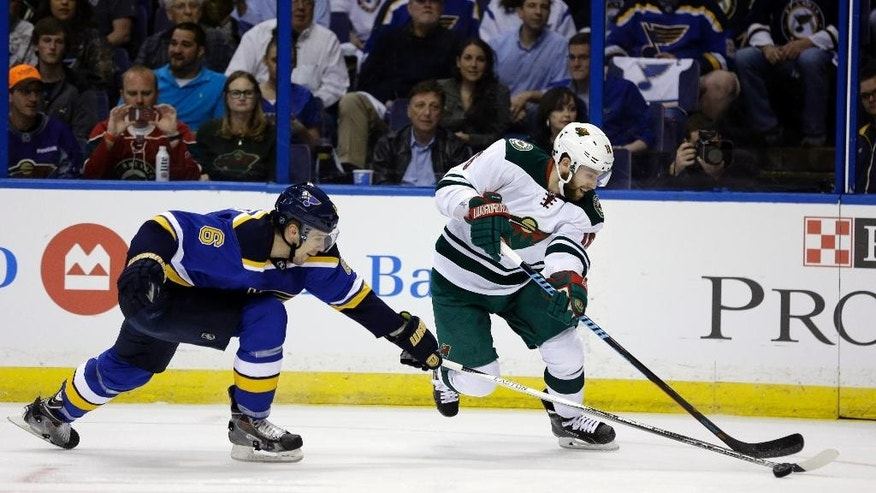 Minnesota Wild's Jason Zucker, right, and St. Louis Blues' Zbynek Michalek, of the Czech Republic, chase after a loose puck during the first period in Game 1 of an NHL hockey first-round playoff series, Thursday, April 16, 2015, in St. Louis. (AP Photo/Jeff Roberson)