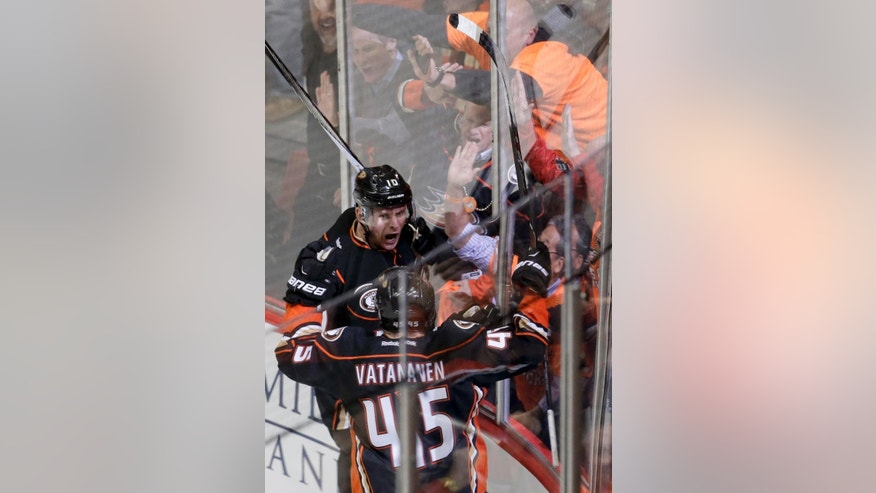 Anaheim Ducks right wing Corey Perry, top, celebrates his first goal with defenseman Sami Vatanen against the Winnipeg Jets during the third period of Game 1 of a first-round NHL hockey playoff series in Anaheim, Calif., Thursday, April 16, 2015. (AP Photo/Chris Carlson)