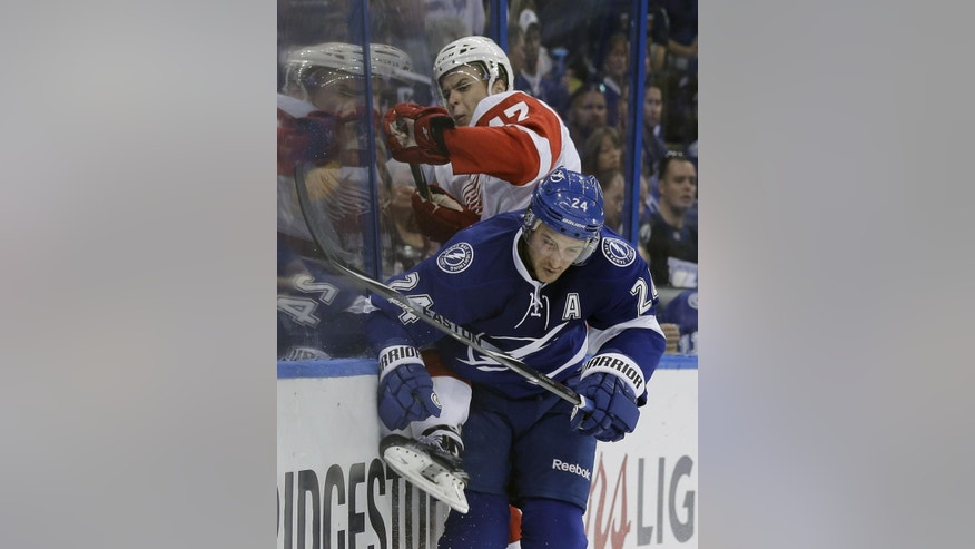 Tampa Bay Lightning right wing Ryan Callahan (24) checks Detroit Red Wings defenseman Alexei Marchenko (47), of Russia, into the boards during the second period of Game 2 of a first-round NHL Stanley Cup hockey playoff series Saturday, April 18, 2015, in Tampa, Fla. (AP Photo/Chris O'Meara)
